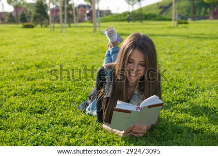 beautiful girl reading a book on vacation lying on the grass - stock photo