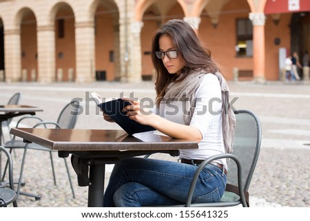Beautiful girl reading a book - outdoor portrait  - stock photo