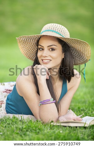 Beautiful girl reading book at the park  - stock photo
