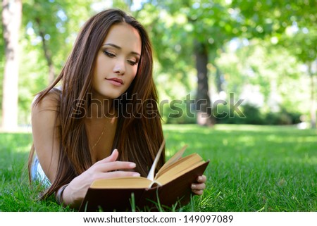 beautiful girl reading book in the summer park