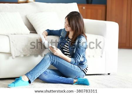 Beautiful girl reading book on carpet, indoor - stock photo