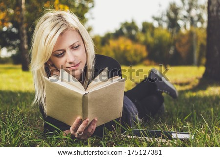 beautiful girl reading in park on grass