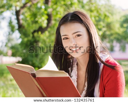 beautiful girl reads book in a park - stock photo