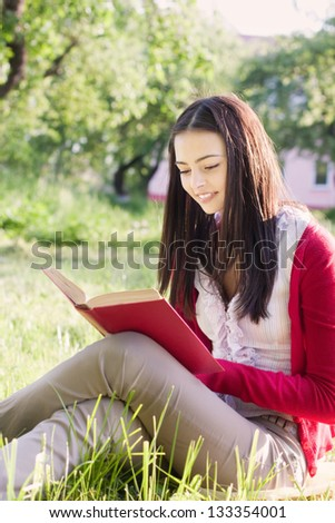 beautiful girl reads book in a park