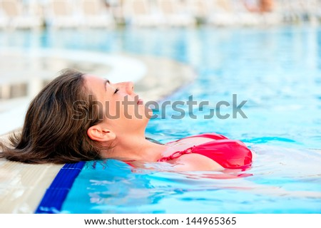 beautiful girl relaxes in the pool with your eyes closed - stock photo
