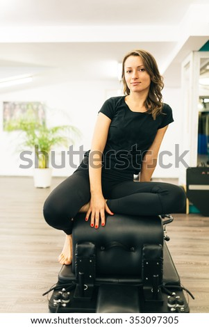 Beautiful girl relaxing after exercising in a pilates room