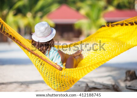 Beautiful girl relaxing at hammock on white beach - stock photo