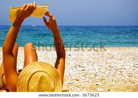 Beautiful girl relaxing by the seaside, reading a novel, in the sun.