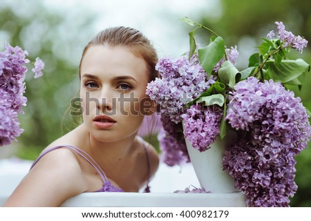 Beautiful girl relaxing in round outdoor bath with lilac flowers, organic skin care
