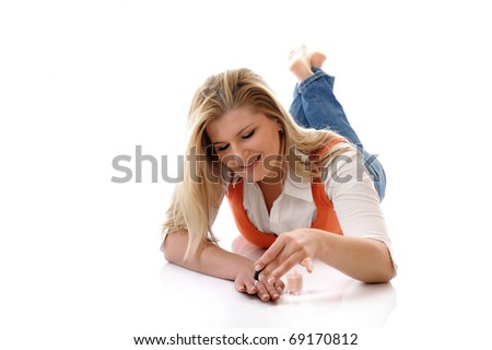 Beautiful girl relaxing lying on the floor and applying nail polish making manicure. isolated on white background