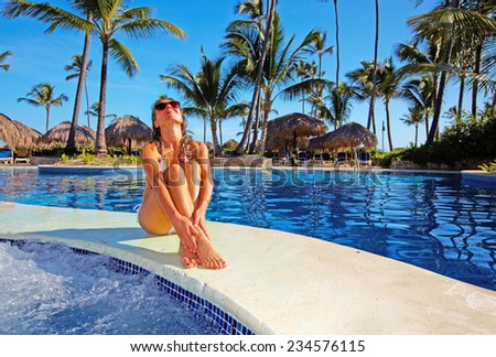Beautiful girl relaxing near swimming pool at luxury resort. - stock photo