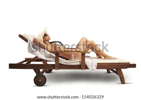 Beautiful girl relaxing on a deckchair in the beach - stock photo
