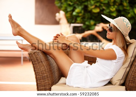 Beautiful girl relaxing on a resort wearing a straw hat - stock photo