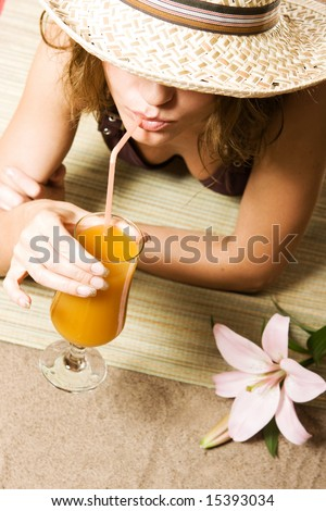 Beautiful girl relaxing on the beach with cocktail - stock photo