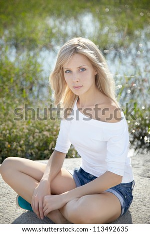 beautiful girl relaxing on the shore of lake.