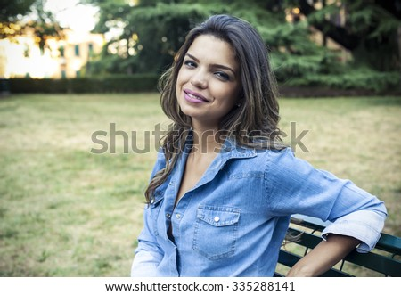 Beautiful girl relaxing outdoor on a bench in a park