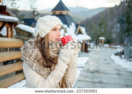 Beautiful girl resting and drinking coffee or tea in winter resort in mountains looking tothe side. Sunset - stock photo