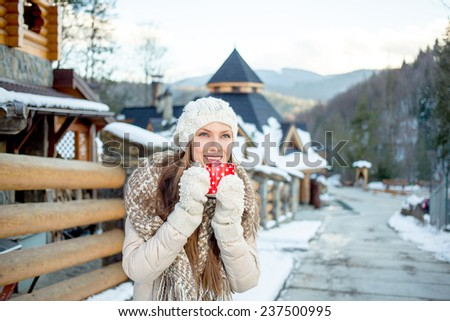 Beautiful girl resting and drinking coffee or tea in winter resort in mountains. sunset - stock photo