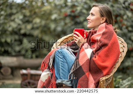 Beautiful girl resting and drinking coffee sitting in autumn garden in chair wrapped in a woolen plaid blanket. copy space - stock photo