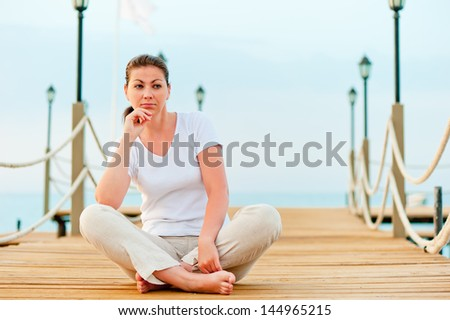 beautiful girl resting on a pier at dawn - stock photo