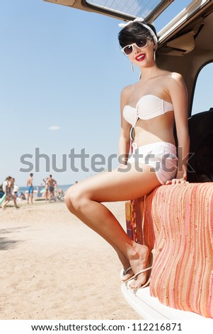 Beautiful girl resting on beach with blue cloudy sky and sun in background - outdoors - stock photo