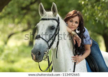 Beautiful girl rides a horse in the summer park - stock photo