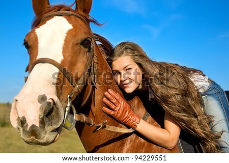 Beautiful girl riding a horse against blue sky - stock photo