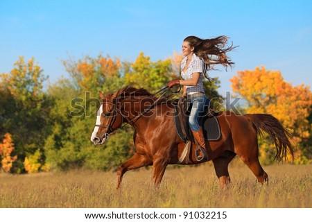 Beautiful girl  riding a horse on autumn field - stock photo
