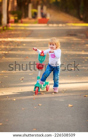 Beautiful girl riding a scooter  - stock photo