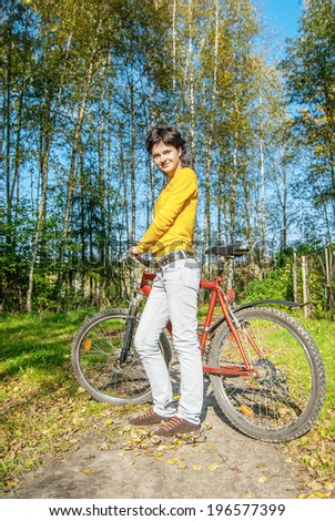 Beautiful girl riding bicycle against autumn nature.