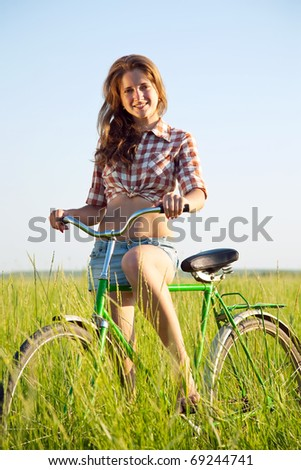 beautiful girl riding bicycle in grass field - stock photo