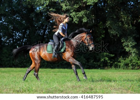 Beautiful girl riding horse in summer evening - stock photo