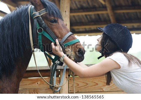 Beautiful girl riding taking a care of a horse on farm - stock photo