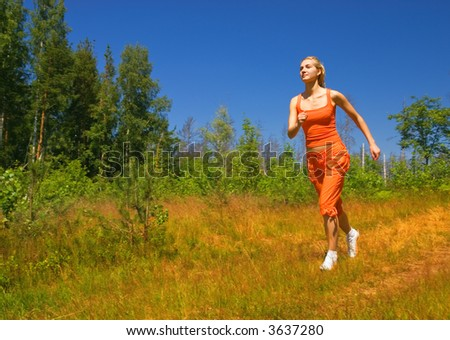 Beautiful girl running in the forest - stock photo