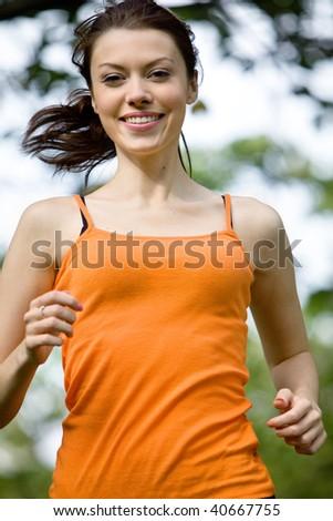 beautiful girl running outdoors looking happy - stock photo