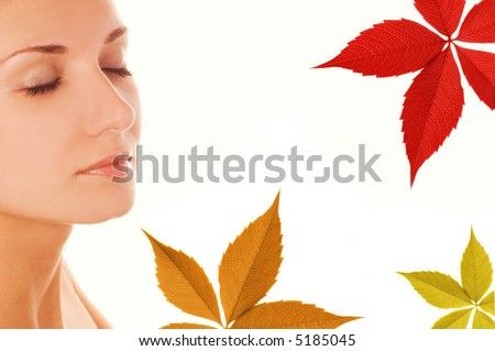 Beautiful girl's face and colorful autumn leaves around her - stock photo