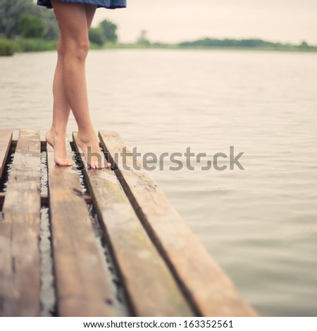 beautiful girl's legs in the morning on the pier - stock photo