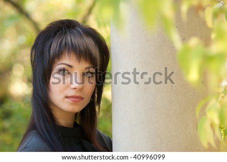 Beautiful girl's portrait near the column with soft background