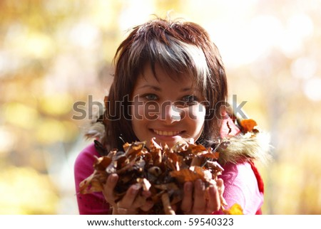 Beautiful girl's portrait with leaves in the autumn park - stock photo