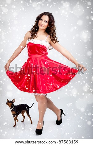 beautiful girl  santa claus clothes  dancing with dog on white background - stock photo