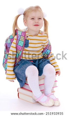 Beautiful girl schoolgirl sitting on a stack of books.Isolated on white background, Lotus Children's Center. - stock photo