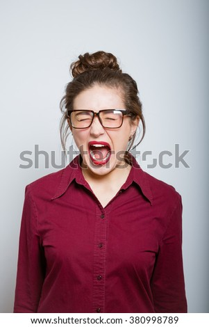 Beautiful girl screaming angry, isolated on gray background