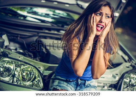 Beautiful girl screaming with despair when realizing that her car broke down.  - stock photo
