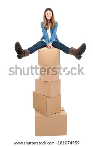 Beautiful girl seated in a pile of cardboard boxes unpacking in new home - stock photo