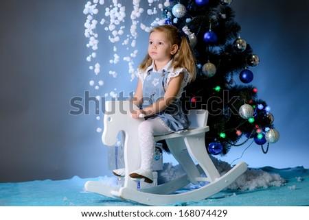 beautiful girl shakes on a horse rocking chair near a Christmas fir-tree - stock photo