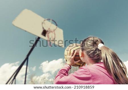 beautiful girl shooting basket and playing basketball, lower view wide angle, VINTAGE - stock photo