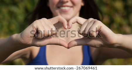 Beautiful girl show love sign outdoor - stock photo