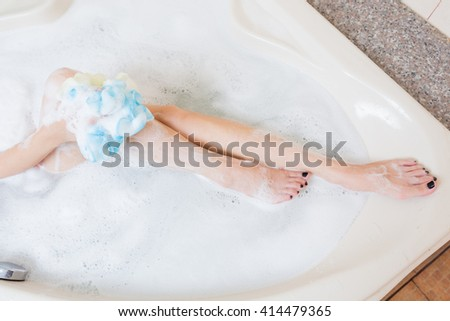 Beautiful girl showering and washing legs in bathtub. - stock photo