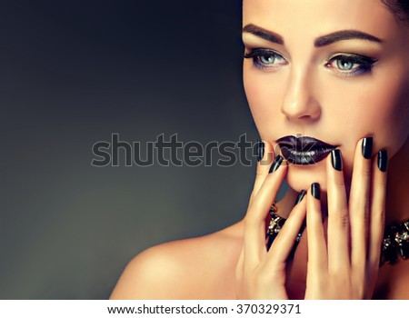 Beautiful girl showing black manicure nails . makeup and cosmetics - stock photo