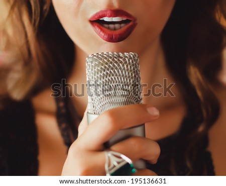 beautiful girl sings into a microphone in the room - stock photo